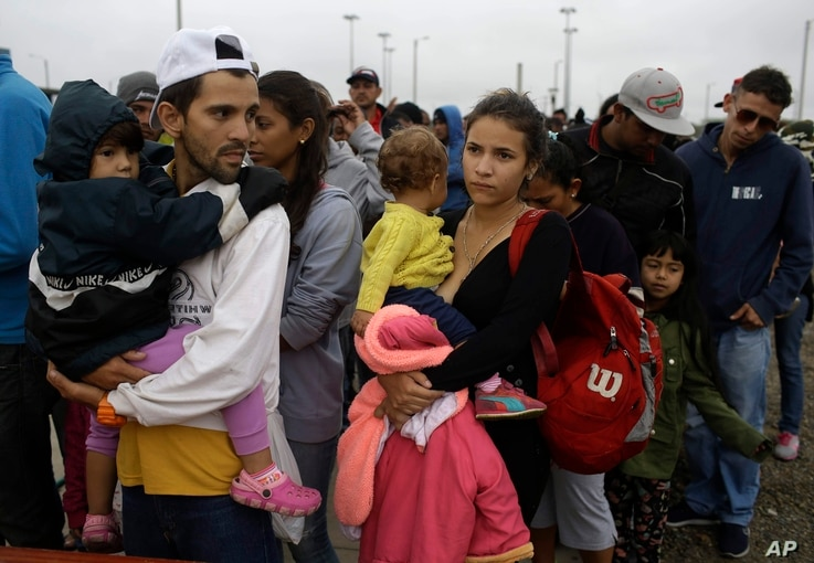 FILE - Venezuelan migrants Jorge Gonzales and his wife Kenia, carrying their boys, wait in line for breakfast, after crossing the border into Peru before the deadline on new regulations that demand passports from migrants in Tumbes, Peru, Aug. 24, 20...