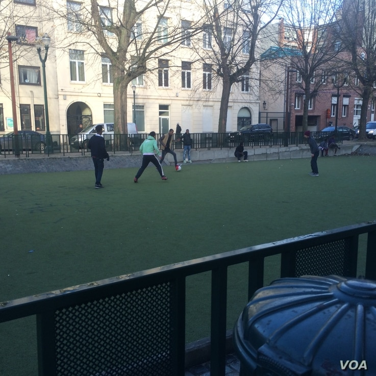 Refugees play football Nov. 23, 2015, near a Brussels camp. The soldiers and tanks guarding the city were not in the neighborhood. (Heather Murdock/VOA)