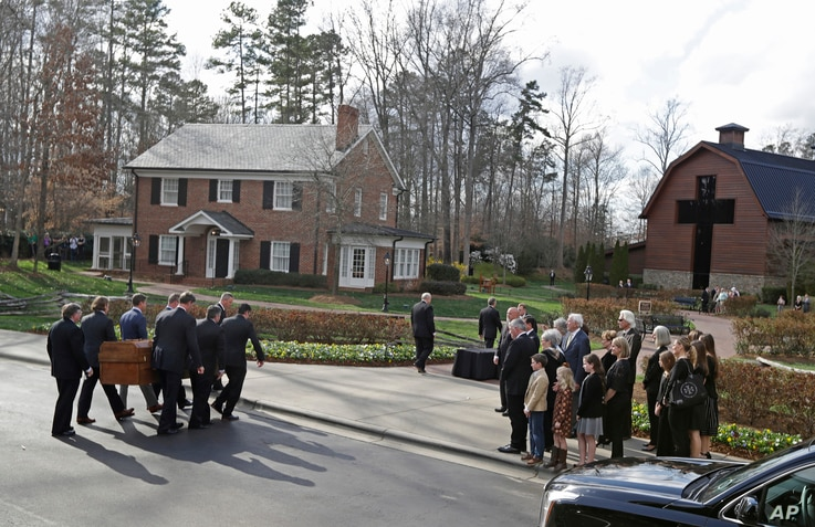 Pall bearers carry the casket carrying the body of Billy Graham past family members to the Billy Graham Library in Charlotte, N.C., Feb. 24, 2018. Graham's body was brought to his hometown of Charlotte on Saturday as part of a procession expected to ...