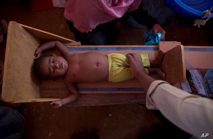 A volunteer measures the height of a Rohingya child at a health center at Balukhai refugee camp near Cox's Bazar, Bangladesh, Jan. 28, 2018.