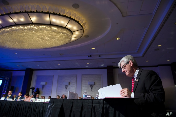 Mississippi Gov. Phil Bryant looks over documents during the opening session of the National Governors Association Winter Meeting in Washington, Feb. 25, 2017.