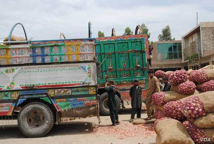 Truckers and their assistants wait in Jalalabad's heat as produce is loaded onto trucks headed across the border into Pakistan, May 16, 2012. (Bethany Matta/VOA)