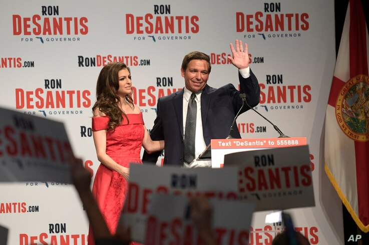Florida Republican gubernatorial candidate Ron DeSantis, right, waves to supporters with his wife, Casey, at an election party after winning the Republican primary, Aug. 28, 2018, in Orlando, Florida.