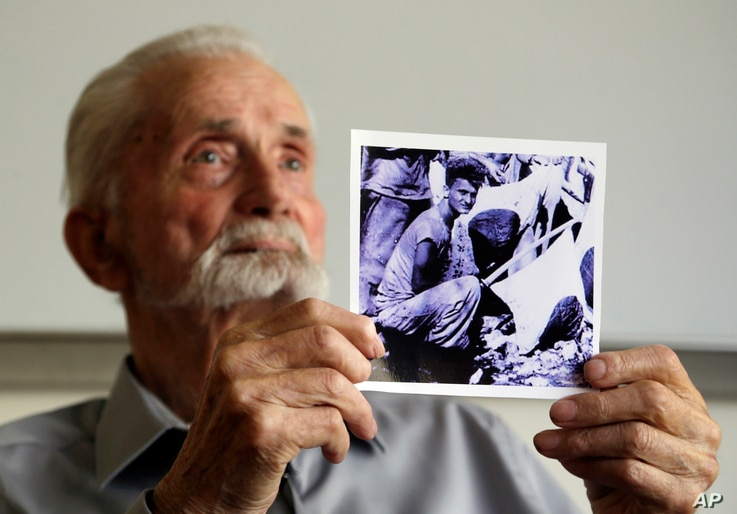 In this Monday, Aug. 7, 2017 photo, WWII veteran Marvin Strombo holds up a photo of himself taken during the battle on Saipan with him holding a captured sword and flag in Portland, Ore.