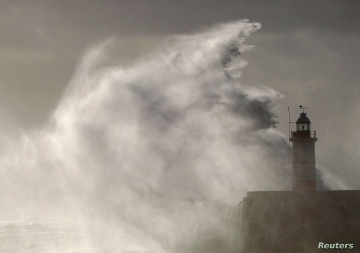 Waves crash against a lighthouse at Newhaven, southeast England, Oct. 28, 2013.