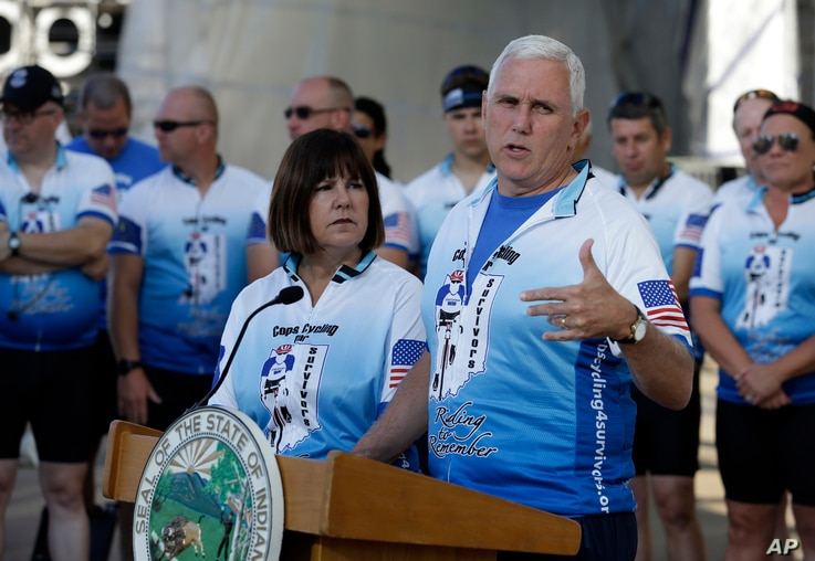 Indiana Gov. Mike Pence speaks as his wife Karen, looks on at the opening ceremony for the Cops Cycling for Survivors fundraising bike ride in Indianapolis, July 11, 2016.