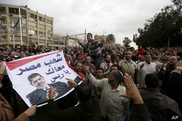 Supporters of Egyptian President Mohammed Morsi chant slogans during a demonstration outside the presidential palace, in Cairo, Egypt, Dec. 5, 2012.