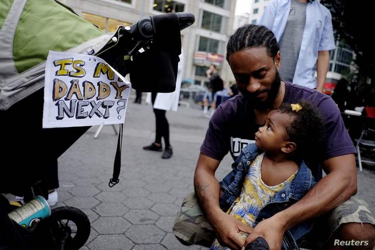 """A man and child take part in a march supporting the Black Lives Matter movement along the streets of Manhattan in New York, July 8, 2016. A sign affixed to a stroller asks, """"Is my daddy next?"""""""