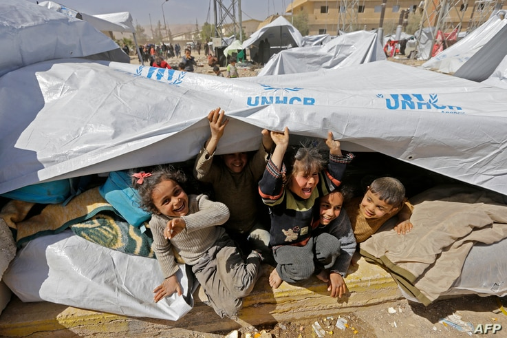 Syrian children, evacuated from rebel-held areas in the Eastern Ghouta, are seen playing at a shelter in the regime-controlled Adra district, on the northeastern outskirts of the capital Damascus on March 20, 2018.