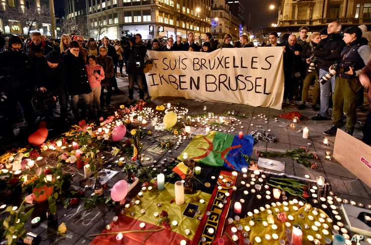 "People hold a banner reading ""I am Brussels"" behind flowers and candles mourn for the terror attack victims at Place de la Bourse in the center of Brussels, March 22, 2016."