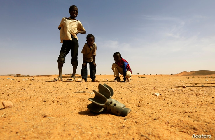 Children look at the fin of a mortar projectile that was found at the Al-Abassi camp for internally displaced persons, after an attack by rebels, in Mellit town, North Darfur March 25, 2014.