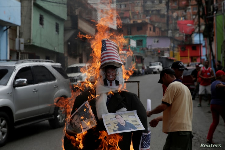 Venezuelan pro-government supporters set fire to an effigy of U.S. President Donald Trump, shown with photos of Argentine President Mauricio Macri, left, and National Assembly leader Julio Borges in Caracas' Enero neighborhood, April 16, 2017.