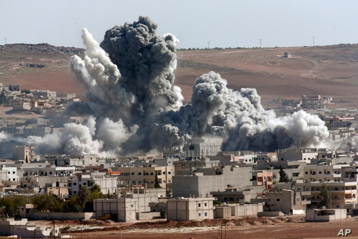 Thick smoke from an airstrike by the US-led coalition rises in Kobani, Syria, as seen from a hilltop on the outskirts of Suruc, Turkey, Oct. 22, 2014.