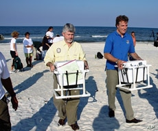 US state and federal wildlife officials Nick Wiley (left) and Tom Strickland carry custom containers with sea turtle eggs to FedEx trucks for delivery to Canaveral National Seashore.
