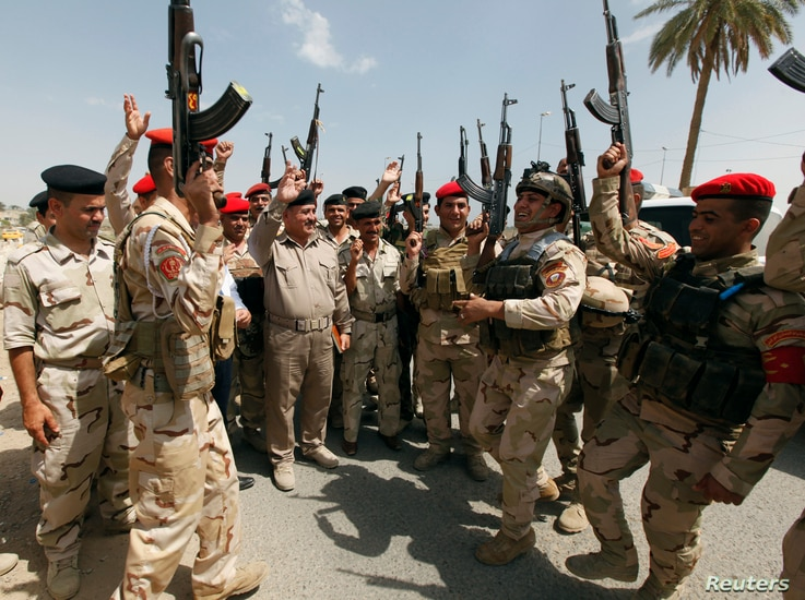 Members of Iraqi security forces chant slogans in Baghdad June 13, 2014.