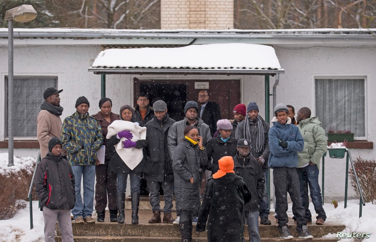 Asylum seekers stand outside an accommodation at a refugee holding centre in the town of Bad Belzig some 135 km (84 miles) south-west of Berlin, December 12, 2012.