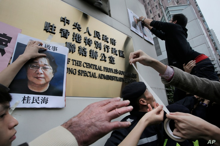 FILE - Protesters try to stick photos of missing booksellers, one of which shows Gui Minhai (L), during a protest outside the Liaison of the Central People's Government in Hong Kong, Jan. 3, 2016.