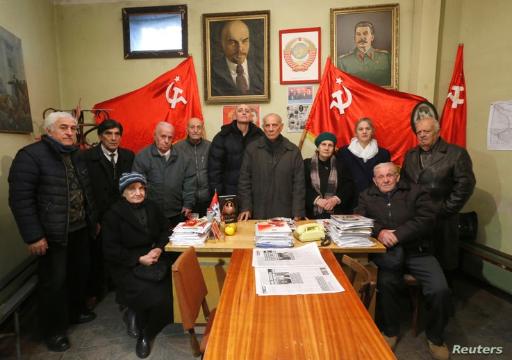 Jiuli Sikmashvili (C), 77, a leader of the United Communist Party of Georgia, poses among other activists before a portrait at the party office in Tbilisi, Georgia, Nov. 30, 2016.