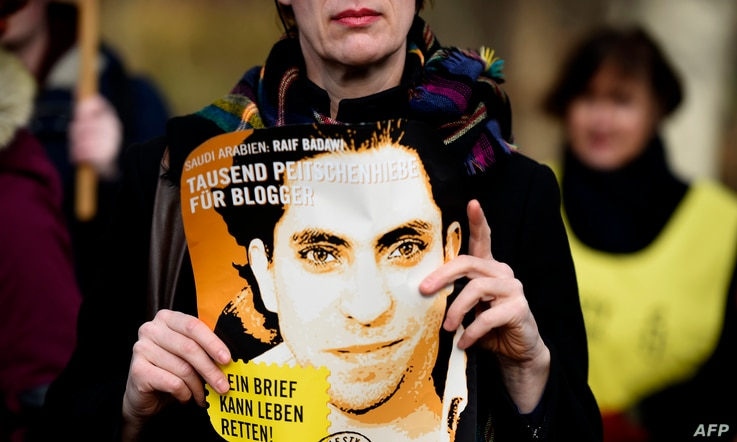 FILE - An Amnesty International activist holds a picture of Saudi blogger Raif Badawi during a protest against his flogging punishment, in front of Saudi Arabia's embassy in Berlin, Germany, January 29, 2015.