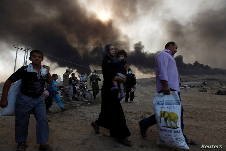 Civilians return to their village after it was liberated from Islamic State militants, south of Mosul in Qayyara, Iraq, Oct. 22, 2016. The fumes in the background are from oil wells that were set ablaze by Islamic State militants.