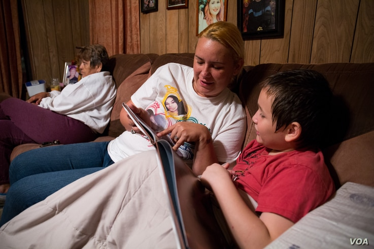 Therese Taylor reads a book to her son before bedtime. Beyond her immediate family, Taylor and her fiance, Andrew Saldivar, have hosted more than 20 people in their Houston home regularly since the storm cleared.