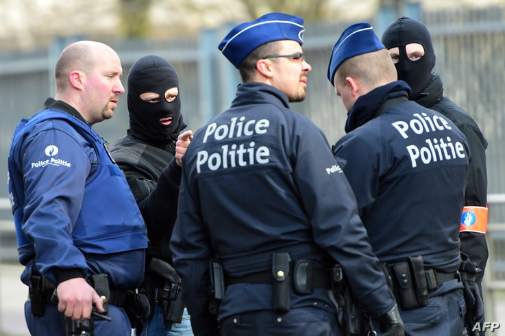 Policemen speak at a security perimeter near Maalbeek metro station, on March 22, 2016  in Brussels, after a blast at this station near the EU institutions caused deaths and injuries.