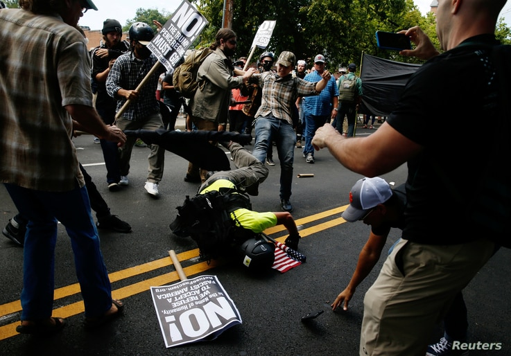 A man hits the pavement during a clash between members of white nationalist protesters against a group of counterprotesters in Charlottesville, Va,, Aug. 12, 2017.