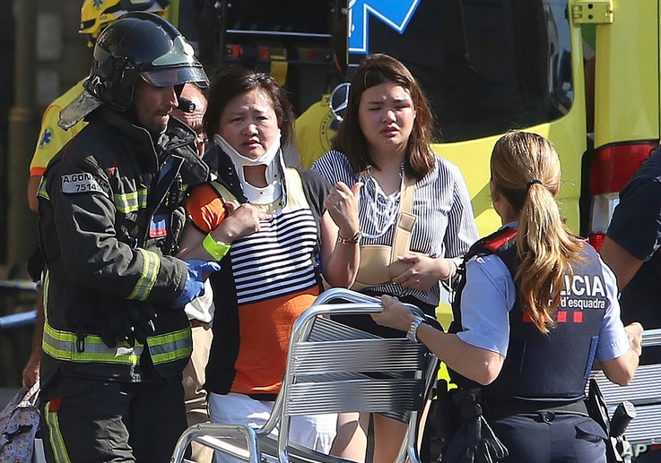 Injured people are treated in Barcelona, Spain, Aug. 17, 2017 after a white van jumped the sidewalk in the historic Las Ramblas district, crashing into a summer crowd of residents and tourists.