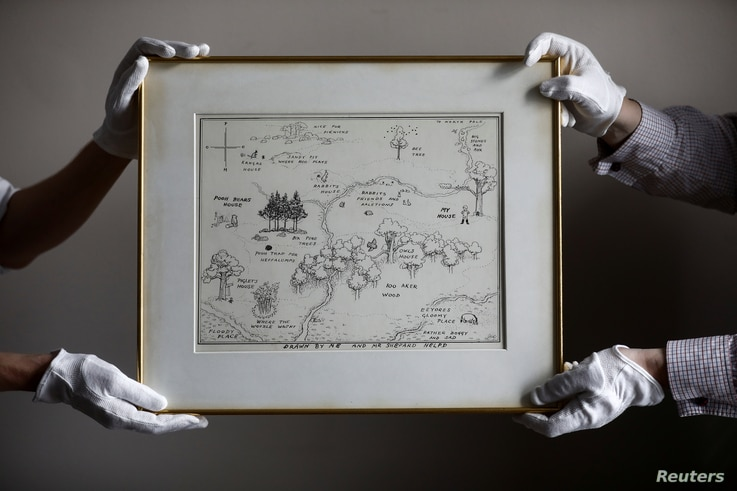 FILE - Sotheby's staff hold the original map of Winnie the Pooh's Hundred Acre Wood by E.H. Shepard at Sotheby's auction rooms in London, Britain, May 31, 2018.
