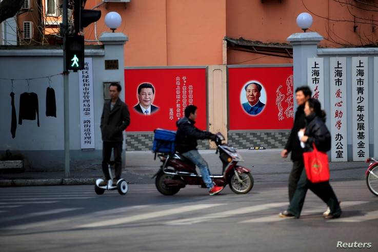 FILE PHOTO: People cross a street in front of posters depicting late Chairman Mao Zedong (R) and China's President Xi Jinping in Shanghai, China, March 1, 2016.