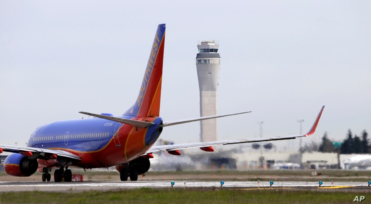 A Southwest Airlines jet waiting to depart in view of the air traffic control tower at Seattle-Tacoma International Airport, April 23, 2013.