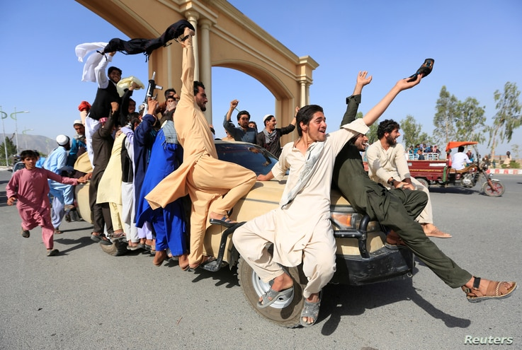 People celebrate a cease-fire in the Rodat district of Nangarhar province, Afghanistan, June 16, 2018.