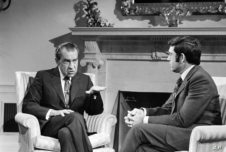 FILE - President Richard Nixon talks with correspondent Dan Rather before an interview at the White House in Washington, Jan. 2, 1972. The two would later have a famously tense exchange during a news conference in March 1974.