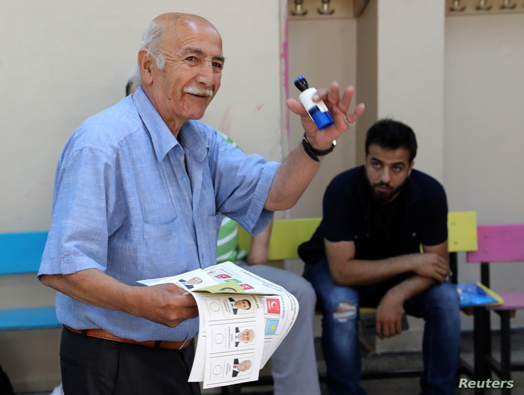 A man gestures as he carries a ballot papers in a polling station located in a school during elections in Istanbul,Turkey, June 24, 2018.