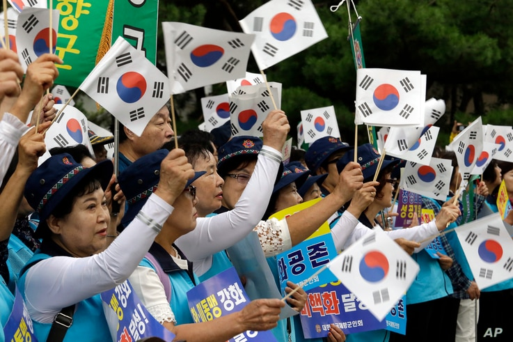 South Koreans wave their national flags during a rally to wish for the successful inter-Korean summit near the presidential Blue House in Seoul, Tuesday, Sept. 18, 2018.