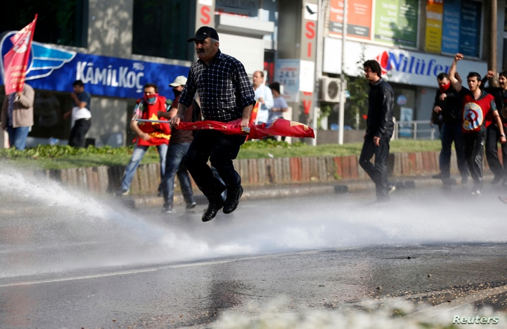 A May Day protester jumps away from a water cannon during clashes between riot police and protesters trying to break through barricades, Istanbul, Turkey, May 1, 2013.
