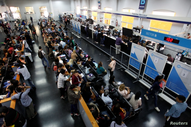 Immigrants wait in line inside the building of National Migration Directorate, in Buenos Aires, Argentina, Feb. 22, 2018.