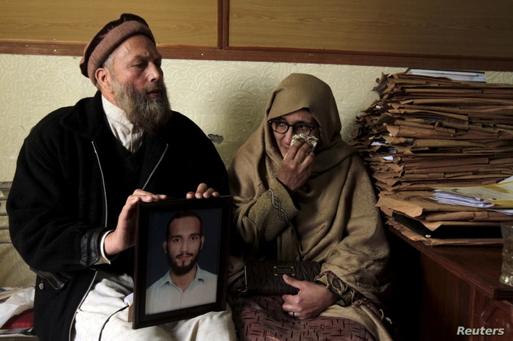 Muhammad Azeem, left, and Sajida Parveen, the parents of Ehsan Azeem, who was sentenced to death by a military court, react while holding their son's picture in Rawalpindi, Jan. 23, 2015. Military documents show Azeem was accused of attacking a milit...