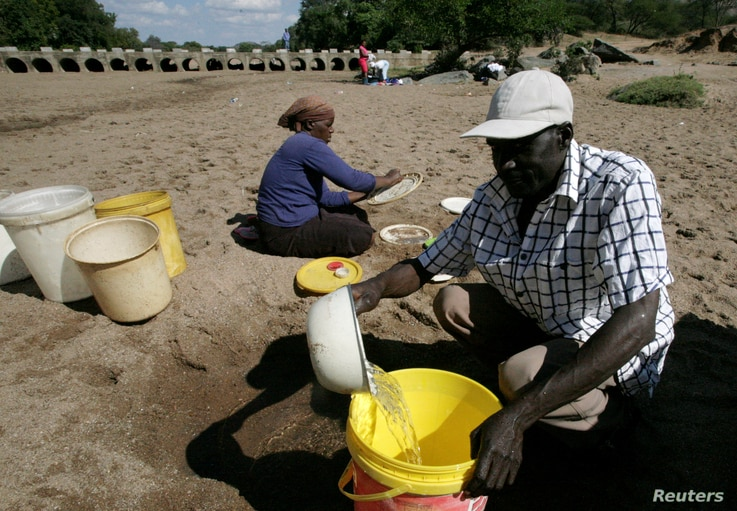 Villagers collect water from a dry river bed in drought hit Masvingo, Zimbabwe, June 2, 2016.