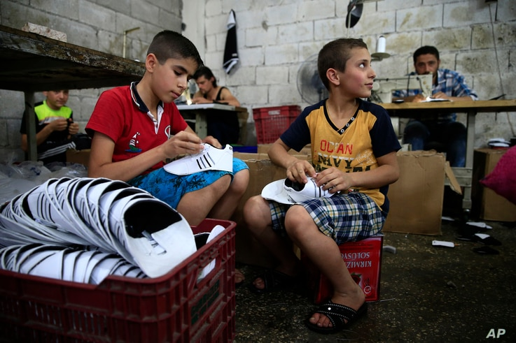FILE - Syrian refugee children Mohammed, left, and Mustafa, 8, right, work at a shoe workshop in Gaziantep, southeastern Turkey, June 2, 2016. According to UNICEF, more than half of Turkey's 2.7 million Syrian refugees are children. Only 325,000 of...
