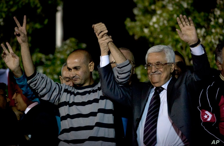 Palestinian President Mahmoud Abbas holds hands of a freed prisoner during a welcome ceremony at the Palestinian Authority headquarters, in the West Bank city of Ramallah, Oct. 30, 2013.
