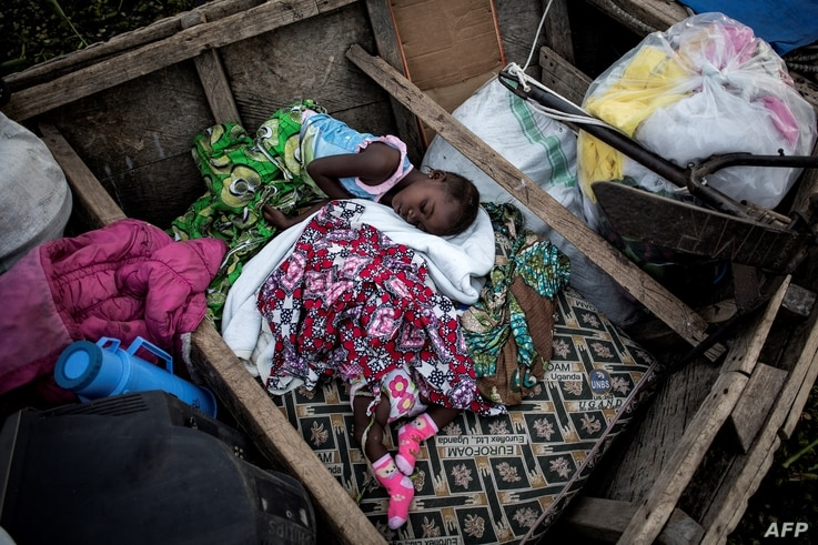 Internally displaced Congolese children sleep in a boat on the shore line of Lake Albert on March 05, 2018 in Tchomia.