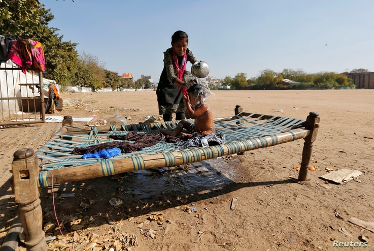 A woman gives a bath to a child on a cot, on the outskirts of Ahmedabad, India, Feb. 1, 2017.