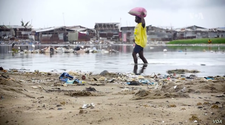 A woman wades near a beach in Monrovia, Liberia. Though poverty does not discriminate, women have fewer resources to cope. (B. Muchler/VOA News)
