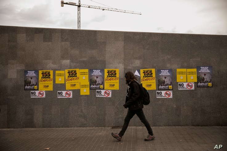 A man walks past posters for the upcoming Catalan regional election in Barcelona, Spain, Monday, Dec. 18, 2017.