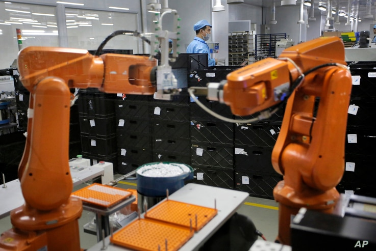 FILe - A Chinese worker is seen behind orange robot arms at work at Rapoo Technology factory in southern Chinese industrial boomtown of Shenzhen, Aug. 21, 2015.