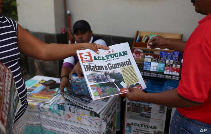 """A man buys a newspaper carrying the Spanish headline """"They killed Gumaro!"""" on the sidewalk in Acayucan, Veracruz state, Mexico, Wednesday, Dec. 20, 2017."""