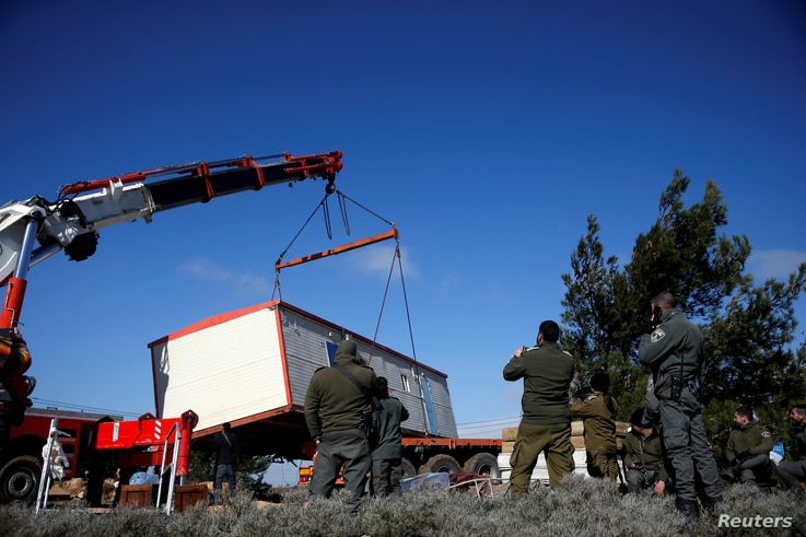 A pre-fabricated home is lowered onto a tow truck as it is removed during an evacuation by Israeli paramilitary police of Jewish settlers from Amona, an illegal outpost in the Israeli-occupied West Bank, Jan. 3, 2019.