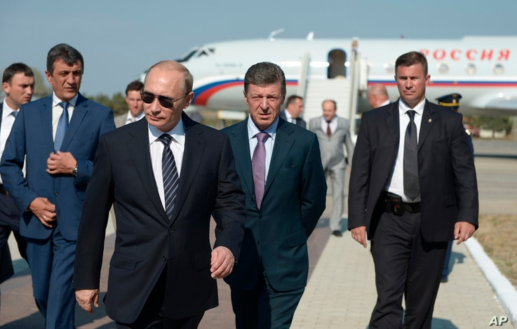 FILE - Dmitry Kozak (2-R), now deputy prime minister of Russia, is seen walking with President Vladimir Putin (2-L) at Belbek airport in Russia-annexed Crimea, Aug. 13, 2014. Kozak is also on Spain's list of suspects tied to organized crime.