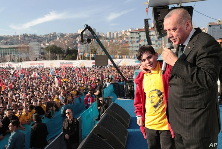 Turkey's President Recep Tayyip Erdogan reacts with a boy as he addresses the supporters of his ruling Justice and Development Party during a rally in Kocaeli, Turkey, March 19, 2019.
